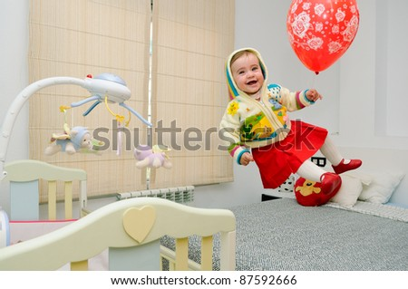 Baby girl flying with a red balloon in her bedroom