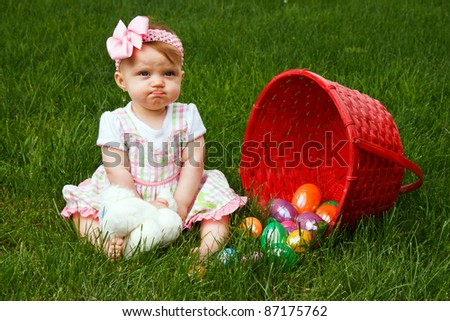 Baby girl frowning beside a spilled Easter egg basket