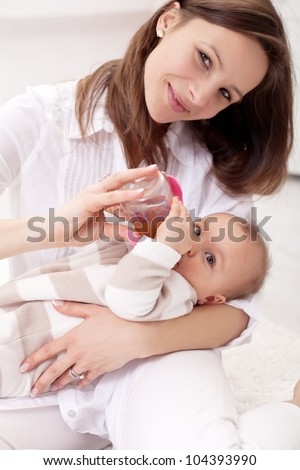 Baby girl held by her mother - drinking from nursing bottle
