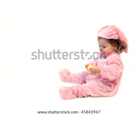 Baby girl hold a yellow Easter egg and tries to open it.  She is dressed in a pink bunny costume and sitting besides a bed of green grass with colorful Easter eggs.