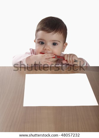 Baby girl holding a pen and sitting in front of a sheet of paper