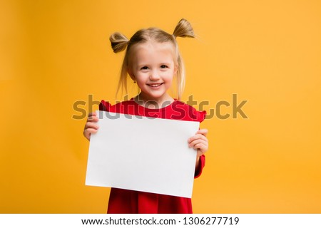 baby girl holding white sheet.Cute little girl with white sheet of paper.yellow background.copy spase.Little girl holding empty sheet of a paper