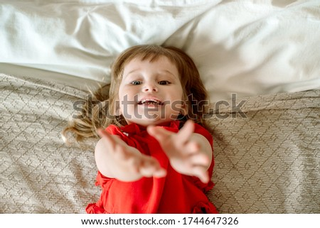 Baby girl holds out her hands with a request. bad mood, cries and asks, insists and demands. lying on the bed. asks for help.Top View Stock photo ©