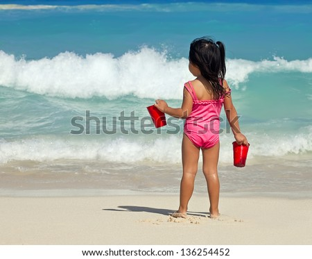 baby girl in a pink swimsuit near the sea - stock photo