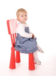 baby girl in blue skirt sitting on chair