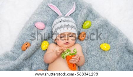 baby girl in bunny hat lying on ...