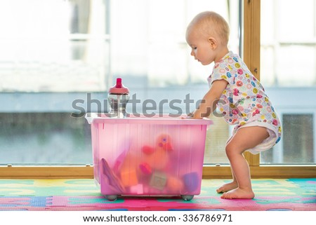 baby girl in creche kids room with big box of toy toys