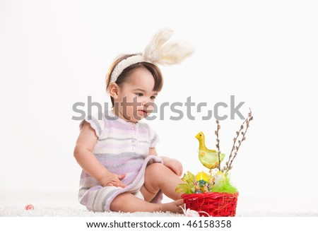 Baby girl in easter bunny costume, playing with chicken in easter basket. Isolated on white background.