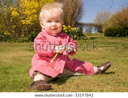 baby girl in garden with flowers. cute female child outside on grass in spring or early summer
