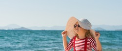 Baby girl in hat and sun glasses on the summer beach. Kid in striped t-shirt on the sea.
