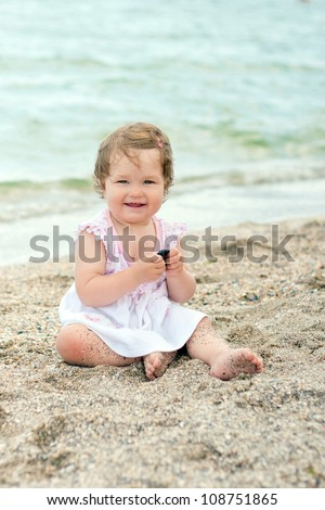 Baby Girl In Pink And White Dress Sitting In The Sand On ...