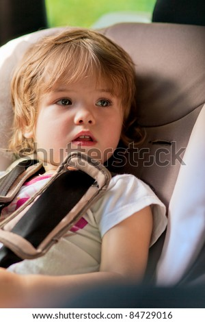 baby girl in safety seat fastened with belt looking up