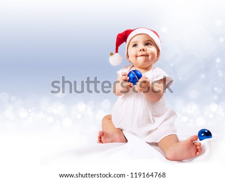 Baby girl in santa\'s hat with blue ornament balls sitting over light blue background