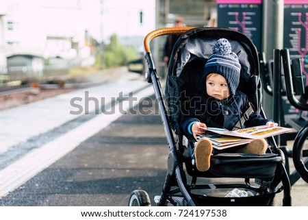 Baby girl in stroller reading a book on a train station in Stockholm, Sweden