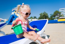 Baby girl in sunglasses on the beach playing with her toys