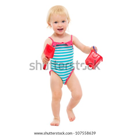 Baby girl in swimsuit holding bucket and shovel