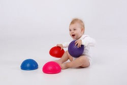 baby girl in white bodysuit with physiotherapy tools for flat feet-balance pod on white background