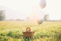 Baby girl in wicker basket with balloons in sunlight in autumn time. Happy child in field on nature on sunset. Family outdoors in fall. Photo of childhood, dreams, holidays, family values.