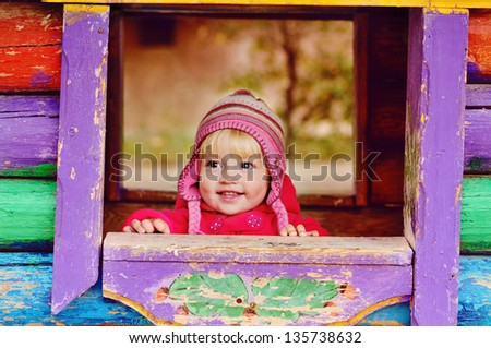baby girl in wooden house on the playground