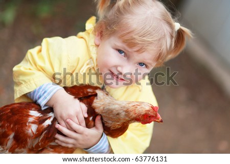 Baby girl in yellow holding hen