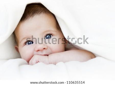 baby girl is hiding under the white blanket