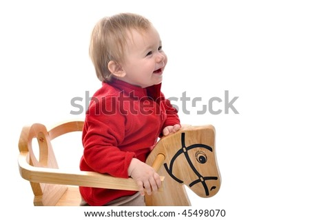 baby girl is riding toy horse over white background