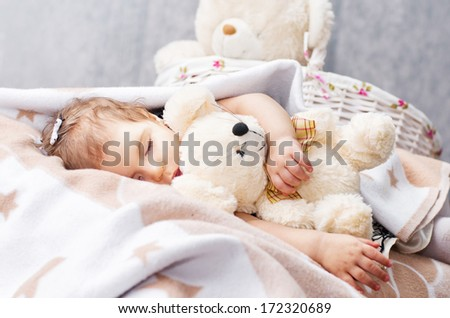 baby girl is sleeping in an embrace with a teddy bear ,