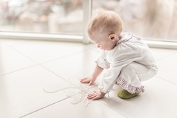 baby girl is touching by her hands a spilled water on the floor