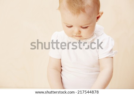Baby girl looking down, studio shot
