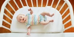 Baby girl lying in co-sleeper attached to parents' bed