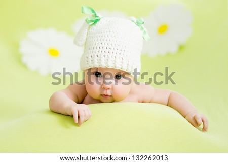 baby girl lying on green meadow among daisy