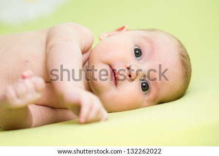 baby girl lying on her side over green background
