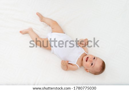 baby girl 6 months old lying on the bed in the nursery on her back upside down, baby morning, baby products concept Foto stock ©