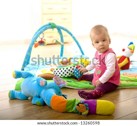 Baby Girl (9 months old) sitting on floor and playing with toys at home in living room. Toys are property released.