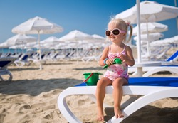 Baby girl on the beach with toys