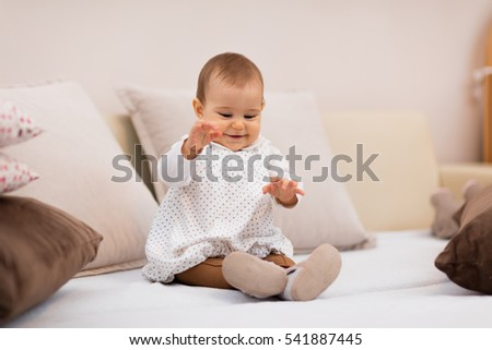 baby girl on the bed among pillows / Playful baby sitting on the bed and playing #541887445