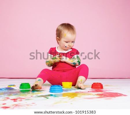 Baby girl painting with hands in studio