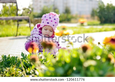 baby girl picking flowers in the park