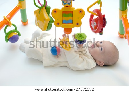 Baby girl playing baby gym