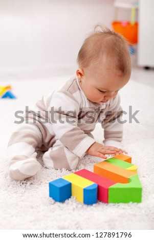 Baby girl playing eith wooden blocks sitting on the floor
