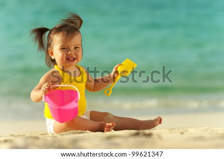 Baby girl playing in the sand on the beach. Ocean as background