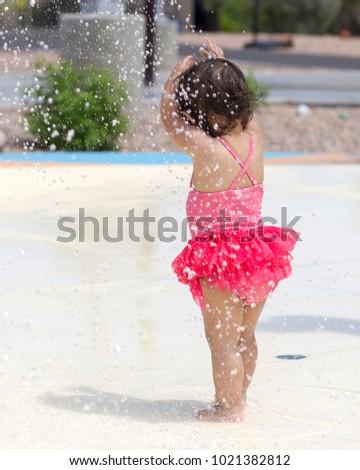 Baby Girl Playing on a Splash Pad #1021382812