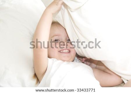 Baby girl playing peek a boo under pillow