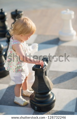 Baby girl playing with chess