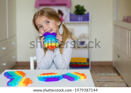 baby girl playing with rainbow pop it fidget. The Push bubble fidget touch toy is a washable and reusable silicone toy. Anti-stress toy for an autistic child. The concept of mental health popit toy
