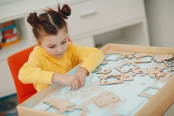 Baby girl playing with sand form toy. Early age education. Toddler cognitive psychology concept