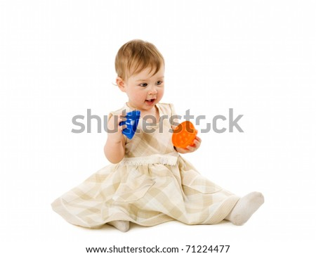 Baby girl playing with toy wearing pink dress isolated