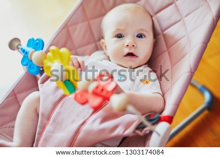 Baby girl playing with toys in bouncer. Little child having fun. Activities for infants