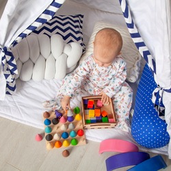 Baby girl playing with wooden cubes in a white children's shelter. Montessori pedagogy. Games for kids, preschool education. Kindergarten, short-stay group.