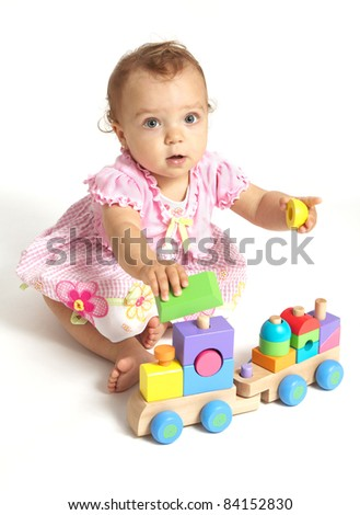 Baby girl playing with wooden train toy